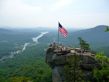 The American Flag waves proudly on top of Chimney Rock with scenic Lake Lure in the background.